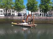 Minigraver op ponton voortgeduwd door bootje